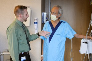 Michael Forbes, a product designer at the Henry Ford Innovation Institute, talks with patient Ismail Khalil, M.D., a vascular surgeon from Lebanon who traveled to Henry Ford Hospital for a liver transplant. Dr. Khalil is wearing the new patient gown.